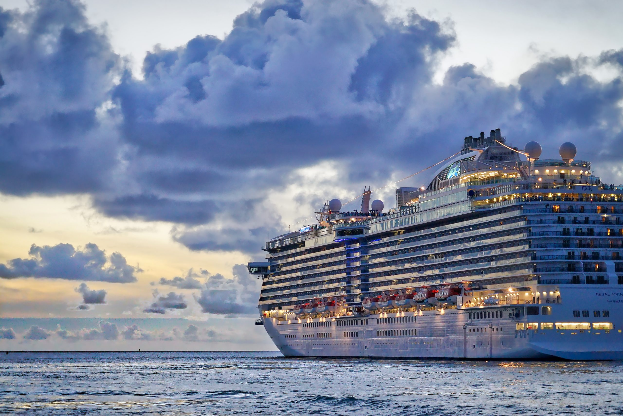 Large commercial cruise ship with lights on at sunset